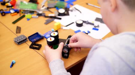 платформа : close-up, childrens hands hold a multicolored small robot, machine, assembled from a designer. children are fond of robotics, programming, modeling, Стоковые видеозаписи