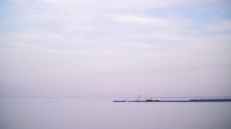 pontão : pier, red sea is calm, windless weather, there are clouds in the sky, you can see a long pier on the horizon Vídeos