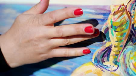 akryl : close-up, female hands of the artist with bright red manicure . she applies paint to the canvas with her fingers, using a special drawing technique. . Dostupné videozáznamy