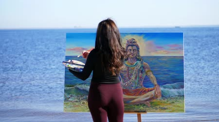unfinished : summer, near river, on the beach. at sunrise, a beautiful woman artist in a tight suit draws a picture. god Shiva is depicted on the picture Stock Footage