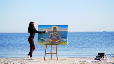 bálvány : summer, near river, on the beach. at sunrise, a beautiful woman artist in a tight suit draws a picture. god Shiva is depicted on the picture Stock mozgókép