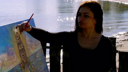 bálvány : summer, near river, on the beach. at sunrise, a beautiful woman artist holds a brush in her hand, draws a picture. she paints on canvas the god Shiva.