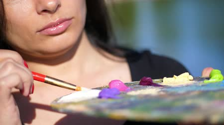 usado : summer,outdoors, close-up of a palette with paints, the woman artist mixes paints with a brush on the palette. Vídeos