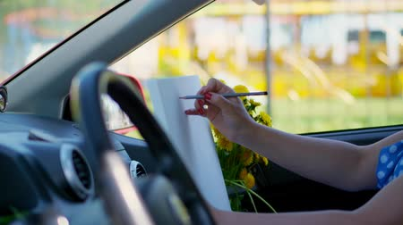 car designer : artist, beautiful brunette woman, sits in car, draws pencil sketch, drawing bouquet of yellow dandelions. drawing from nature, the creative process of drawing. summer Stock Footage