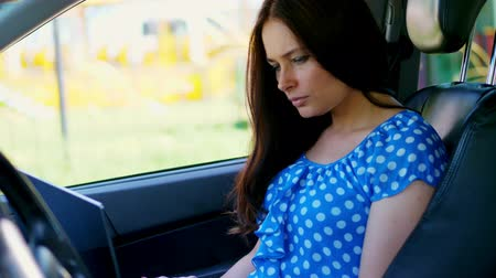 limuzína : beautiful brunette woman in a blue dress, sits in car, is working on laptop, communicating in social networks. uses the Internet, mobile communication