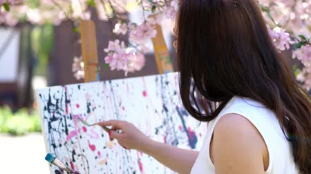 resimlerinde : a beautiful woman painter in white dress, in blooming spring apple orchard, she mixes paints with special small spatula on the pallet. artist paints a picture of flowers