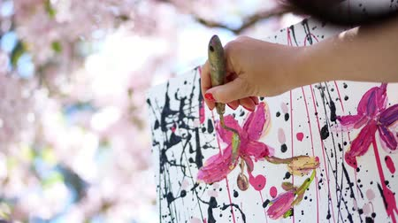 resimlerinde : close-up, female hand, painter, artist paints a picture of flowers in blooming spring apple orchard, she applies paints to canvas with special small spatula, holds palette with paints Stok Video