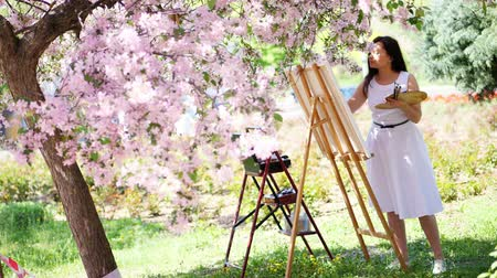 шедевр : a beautiful woman painter in white dress, artist paints a picture of flowers in blooming spring apple orchard, she holds a palette with paints and a brush in her hands Стоковые видеозаписи