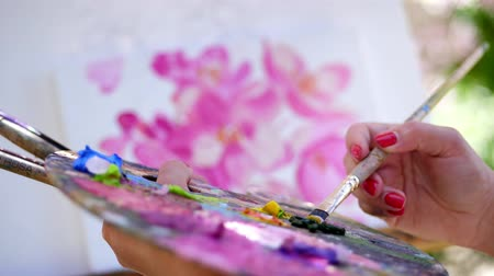 resimlerinde : close-up, female hands, painter, artist paints a picture of flowers , she holds palette with paints and brushes, mixes paints with a brush on the pallet