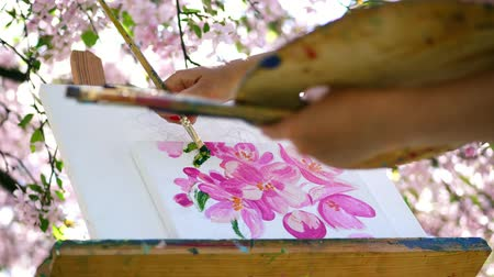 resimlerinde : close-up, painter draw a picture of flowers in blooming spring apple orchard, she paints with brush, holds palette with paints. wind sweeps flowering branches over the easel