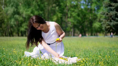 koszorú : summer, beautiful brunette woman in white dress, sits on green lawn, grass, weaves a wreath of yellow dandelions, smiles Stock mozgókép