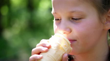 creme : portrait, pretty girl of eight years, blonde, with freckles, eating white ice cream in a waffle cup, licks it with tongue. summer Stock Footage