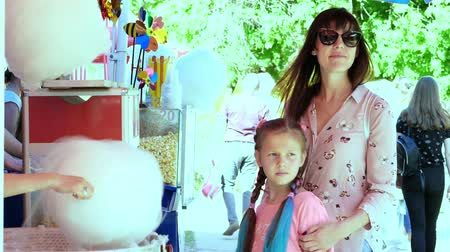 targi : a brunette woman, in sunglasses, with her daughter, a girl of 8 years old, with blue pigtails, waiting while seller making cotton candy, white candyfloss, in the city park, in summer