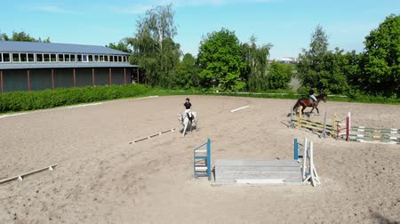 dörtnal : view from above, aerial video shooting, training sand field, playground, riders, jockeys ride horses, perform various exercises with horses, next to barriers. summer, outdoors,