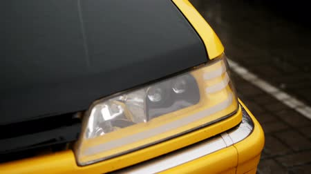 clear liquid : close up, headlamp of car. shower, heavy drops fall with Water splashes, on wet surface of black and yellow car hood standing in parking lot. car gets wet under heavy rain, Stock Footage