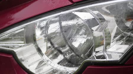 reflektör : close up, headlamp of car. shower, heavy drops fall with Water splashes, on wet surface of red car hood, glass headlamp . car gets wet under heavy rain,
