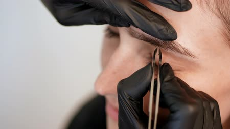 tweezing : beauty saloon. close-up, hands of the cosmetician in black rubber gloves hold tweezers and pull out eyebrows. Master corrects the shape of the eyebrows