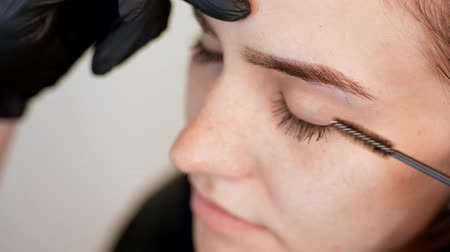 tweezing : beauty saloon. close-up, hands of the cosmetician in black rubber gloves keep a special brush and comb eyebrows. Master corrects the shape of the eyebrows. Professional care for face.