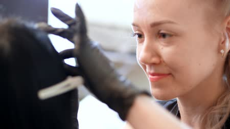manipulacja : beauty saloon. a portrait of a master, a cosmetologist, in black rubber gloves, works with a client, loves her work very much, she is happy. Professional care for face.