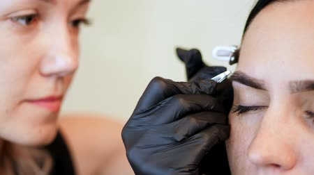 tweezing : beauty saloon. close-up, hands of the cosmetician in black rubber gloves hold tweezers and pull out eyebrows. Master corrects the shape of the eyebrows, tweezing eyebrow