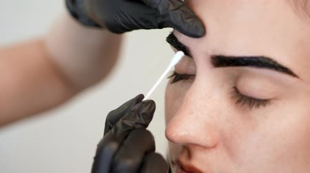 longhair : close-up, the hands of the cosmetologist in black rubber gloves hold a cotton swab and correct the shape of the eyebrows during painting. coloring, eyebrows shaping Stock Footage