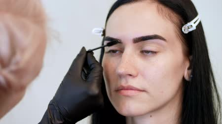 tweezing : beauty saloon. close-up, a beautician in black rubber gloves, gently combs the eyebrows of the client with a special little brush, comb, shapes the eyebrows after staining