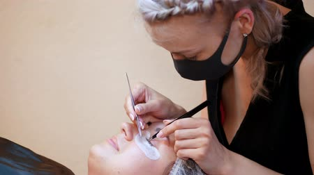 cílios : beauty saloon. procedure for eyelash extension. The master in the bandage on the face, glues each cilium with special glue, works by means of two tweezers