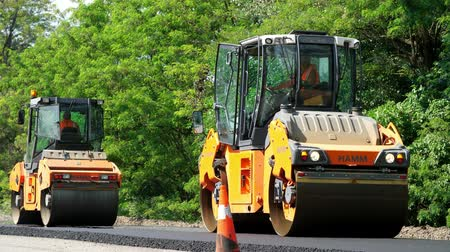 погрузчик : CHERKASSY REGION, UKRAINE - MAY 31, 2018: repair of a highway, Road construction works. roller compactor machine and asphalt finisher laying a new fresh asphalt pavement,