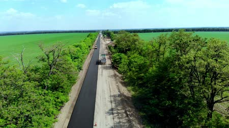pneumatic : Aerial view on the new asphalt road, road repair. there is asphalt laid on one side of the traffic. due to repair, reverse movement works on one side of the road, Stock Footage