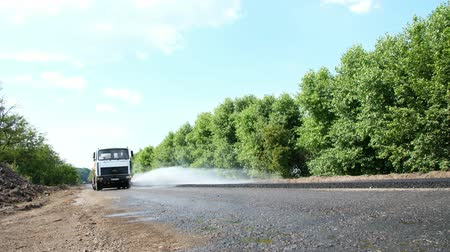 roadworks : CHERKASSY REGION, UKRAINE - MAY 31, 2018: repair of a highway, Road construction works. Special watering machine sprinkles water on new fresh asphalt pavement, covering on one side of the traffic.