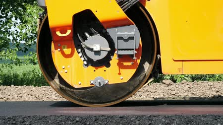 paving : close-up, Road construction works with roller compactor machine and asphalt finisher. Road roller laying fresh asphalt pavement on top of the gravel base during road construction Stock Footage
