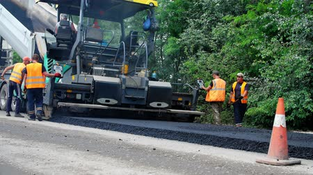 paving : CHERKASSY REGION, UKRAINE - MAY 31, 2018: repair of a highway, Road construction works. workers lay asphalt. There are lots of special equipment, machines for paving asphalt