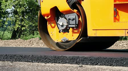 pneumatic : close-up, Road construction works with roller compactor machine and asphalt finisher. Road roller laying fresh asphalt pavement on top of the gravel base during road construction Stock Footage