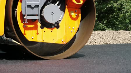 pneumatic : close-up, Road construction works with roller compactor machine , asphalt finisher. Road roller laying fresh asphalt pavement on top of the gravel base during road construction