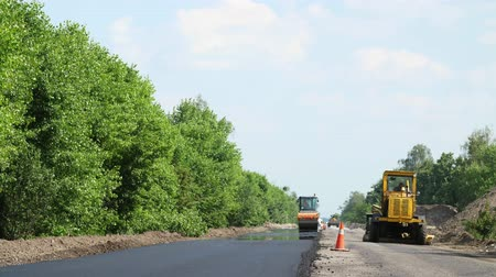 погрузчик : repair of a highway, roller compactor machine and asphalt finisher laying a new fresh asphalt pavement, covering on one side of the traffic. Road construction works