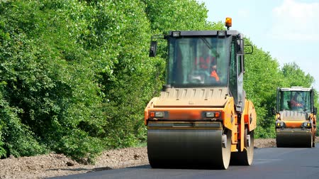 tracked : repair of a highway, roller compactor machine , asphalt finisher laying a new fresh asphalt pavement, covering on one side of the traffic. Road construction works Stock Footage