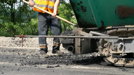 tracked : repair of a highway, Road construction works. worker in an orange waistcoat, a special uniform, with a shovel unloads the car with asphalt Stock Footage
