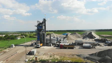 mixer : CHERKASSY REGION, UKRAINE - MAY 31, 2018: Aerial view on asphalt plant, the territory of the plant, the mountains of rubble, many kamazes, trucks., Road construction works.
