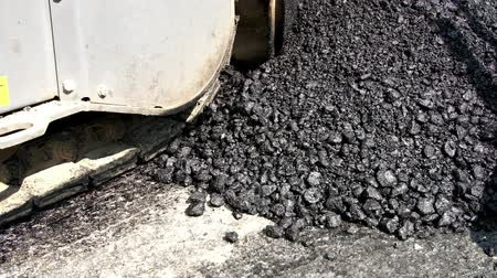 zrnitý : close-up, fresh asphalt in the process of laying on the road,, large lumps, in resin, black, shines in the sun,