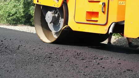 tracked : close-up, Road construction works with roller compactor machine and asphalt finisher. Road roller laying fresh asphalt pavement on top of the gravel base during road construction Stock Footage