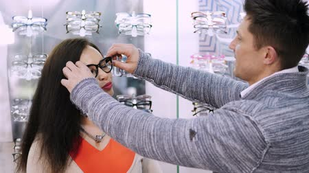 optyk : shop glasses, optics, beautiful couple with poor eyesight, choose their own glasses, rims glasses. Happy couple trying on glasses in shop, Optical Store. health care concept