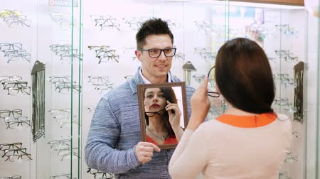 optyk : sexy beautiful woman checking her new glasses in a mirror at in optical store, optics, optician retail store, Eyeglasses shop, Handsome young male salesman holding a mirror