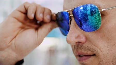 optyk : close-up, portrait of Handsome young man trying on blue sunglasses at optical store, optician retail store. in glasses of spectacles is reflected the showcase of optics with glasses Wideo