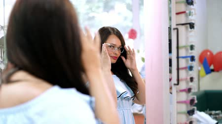 düzeltme : Young sexy woman checking her new glasses in a mirror at optician retail store. Young Woman with Eyeglasses in Optical Store. Beautiful girl wearing glasses in optician shop