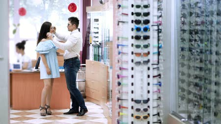 corrections : shop glasses, optics, beautiful married couple choose their own glasses, rims glasses. Happy couple trying on glasses in shop, Optical Store. health care concept