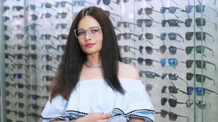 vidro : sexy beautiful woman staring at camera. Portrait of smiling female customer wearing spectacles in optical store, in an optician retail store, . a lot of glasses on the background Vídeos