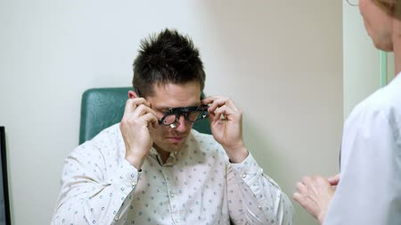 phoropter : young man at a reception with an ophthalmologist, checks vision, having eye examination with phoropter, optometrist trial frame, visual inspection device. in doctors office