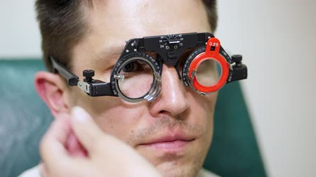 phoropter : face close-up , ophthalmologist examining patient man with optometrist trial frame, visual inspection device. male patient to check vision in ophthalmological clinic,