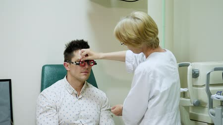 phoropter : Female Optometrist Doing Sight Testing For Patient In Hospital with phoropter, optometrist trial frame, visual inspection device. checks vision in doctors office