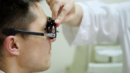 phoropter : Consultation with an ophthalmologist. face close-up , ophthalmologist examining patient man with optometrist trial frame, Medical equipment. Coreometry.